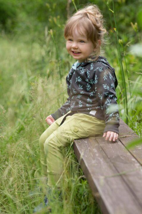 Lachendes Mädchen trägt Kinder Baby grüne Pumphose Haremshose mit Tasche STAY GREEN Print - Braunen Kapuzenpullover mit türkisen Zweige Blätter von Pinokio - Babyphoto Kinderphoto