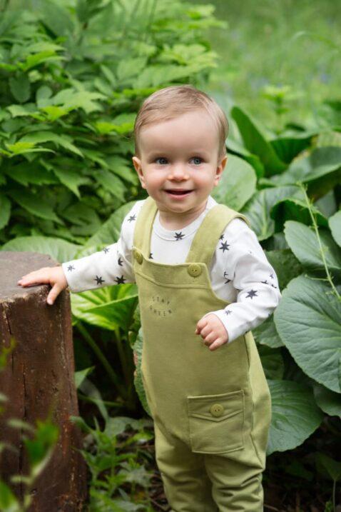 Junge trägt grüne Baby Latzhose mit Tasche & STAY GREEN Print Statement - Weißes Oberteil langarm mit Sterne von Pinokio - Babyphoto Kinderphoto