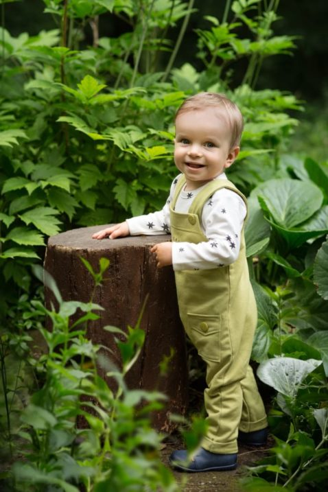 Pinokio Junge trägt weißes BabyLangarm Oberteil mit Sterne - Grüne Kinder Trägerhose Babyhose lang mit Tasche & STAY GREEN Print - Babyphoto Kinderphoto