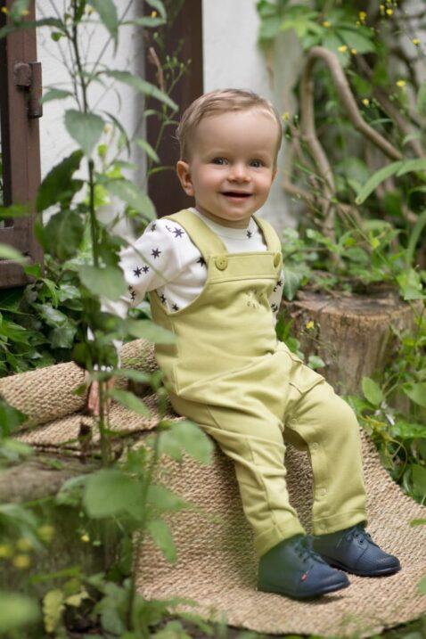 Sitzender Junge trägt weißes Baby Langarmshirt mit Sterne - Grüne Limette Lindgrün Kinder Latzhose mit Tasche & Stay Green Aufschrift von Pinokio - Babyphoto Kinderphoto