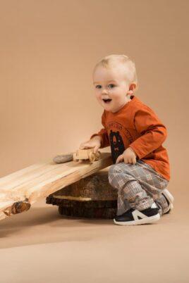 Spielender Junge trägt braunes Baby Langarmshirt Oberteil mit Bär Motiv Bear Club - Kinderhose Babyhose im Schottenmuster kariert Grau von Pinokio - Babyphoto Kinderphoto