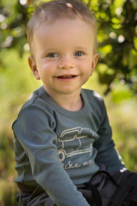 Lachender Junge trägt blau grünen Babybody langarm mit Auto - Retro Vintage Baby Kinder Pumphose Haremshose in Braun Grau Graphit von Pinokio - Babyphoto Kinderphoto