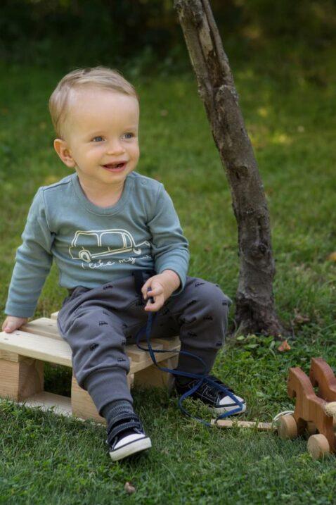 Sitzender Junge trägt blaugrünen Baby Langarmbody mit Car Automobile - Vintage Retro braune Baummwoll Haremshose Babyhose für Kinder von Pinokio - Babyphoto Kinderphoto