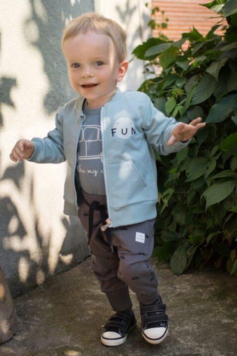 Stehender Junge trägt braune Auto Pumphose - Blau Grünen Baumwoll Babybody langarm Retro-Auto - FUN Sweatjacke mit Taschen & Streifen türkis grün von Pinokio - Babyphoto Kinderphoto