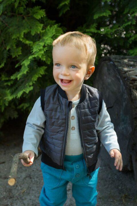Lachender Junge trägt blau gestreiften Baby Polo Langarmbody - Schwarze Steppweste mit Auto Patch - Türkise Babyhose mit Taschen & Knöpfe von Pinokio - Babyphoto Kinderphoto