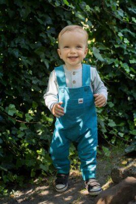 Lachender Junge trägt türkis blaue Latzhose Babyhose mit Tasche & Vehicle Automobile Patch - Baumwollbody blau gestreift mit Holz Knöpfe von Pinokio - Babyphoto Kinderphoto