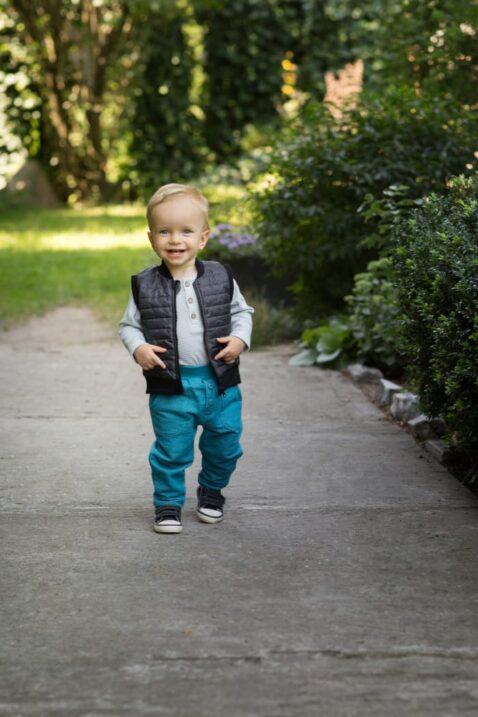 Laufender Junge trägt türkise Babyhose mit Taschen & Knöpfe - Kinder Steppweste schwarz mit Auto-Patch - Blau gestreifter Baby Baumwollbody langarm von Pinokio - Babyphoto Kinderphoto