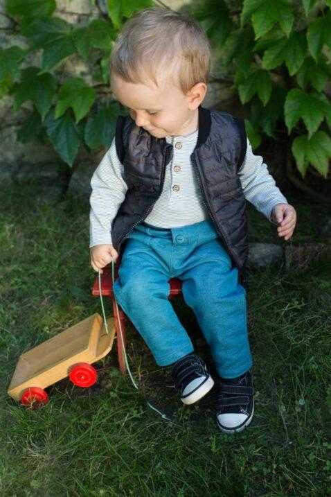Spielender Junge trägt schwarze Kinder Steppweste - Türkise Car Babyhose mit großen Taschen - Babybody mit blauen Streifen & Retro Auto Patch von Pinokio - Babyphoto Kinderphoto