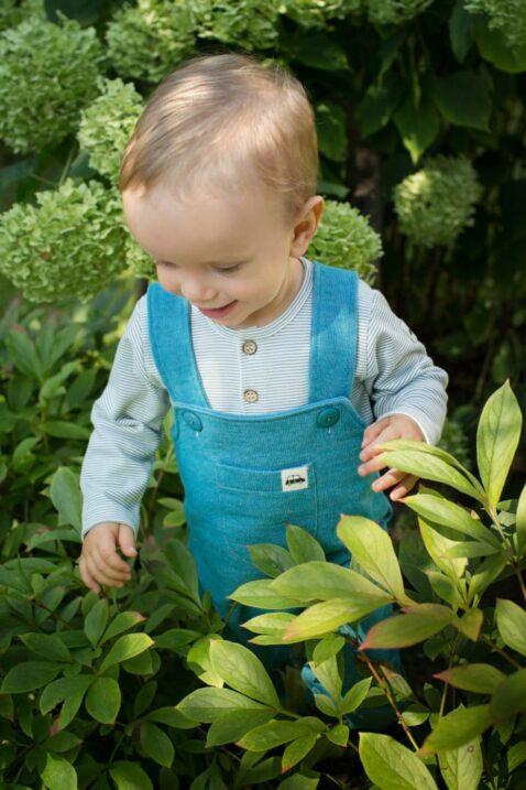 Staunender Junge trägt blau gestreiften Polo Babybody langarm - Türkise grüne Kinder Latzhose mit Auto Patch & Tasche von Pinokio - Babyphoto Kinderphoto
