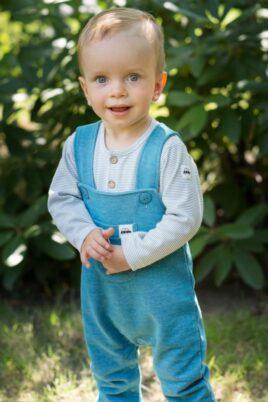 Stehender Junge trägt türkise Baby Kinder Latzhose mit Auto Patch & Tasche - Blau gestreiften Polo Langarmbody mit Knöpfe von Pinokio - Babyphoto Kinderphoto