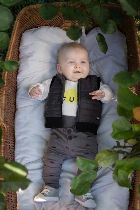 Lachender Junge trägt graue Baby Leggings Schlupfhose mit Autos, Bündchen & Knöpfe - Schwarze Steppweste Patch - Wickelbody weiß FUN Smiley von Pinokio - Babyphoto Kinderphoto