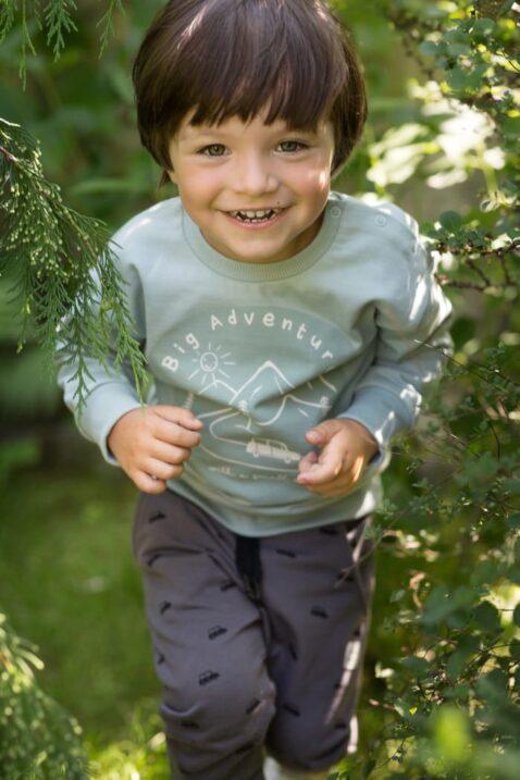 Lachender Junge trägt blau mint-grünen Langarm Baby Pullover Rundhals mit Berge, Autos & Print ADVENTURE - Graue Pumphose mit Taschen & Autos von Pinokio - Babyphoto Kinderphoto