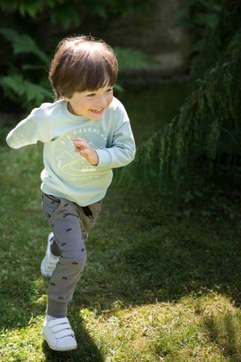 Rennender Junge trägt mintgrünes Baby langarm Sweatshirt BIG ADVENTURE Print - Hochwertige graue Haremshose mit Taschen & Autos gemustert von Pinokio - Babyphoto Kinderphoto