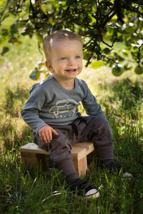 Sitzender Junge trägt blau-grünen Babybody langarm mit Auto - Pumphose mit Taschen, Komfortbund & Bündchen in Grau Braun von Pinokio - Babyphoto Kinderphoto