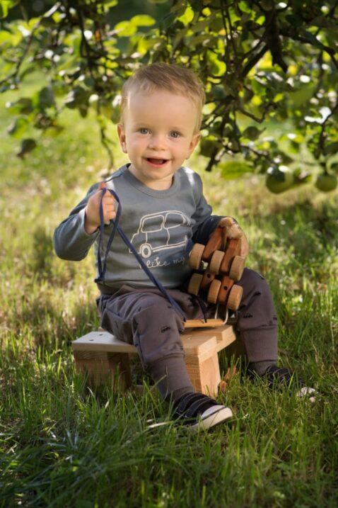 Spielender Junge trägt blaugrünen Baby Auto Langarmbody - Haremshose mit Taschen, Kordel, Gummizug & Cars gemustert in Dunkelgrau von Pinokio - Babyphoto Kinderphoto