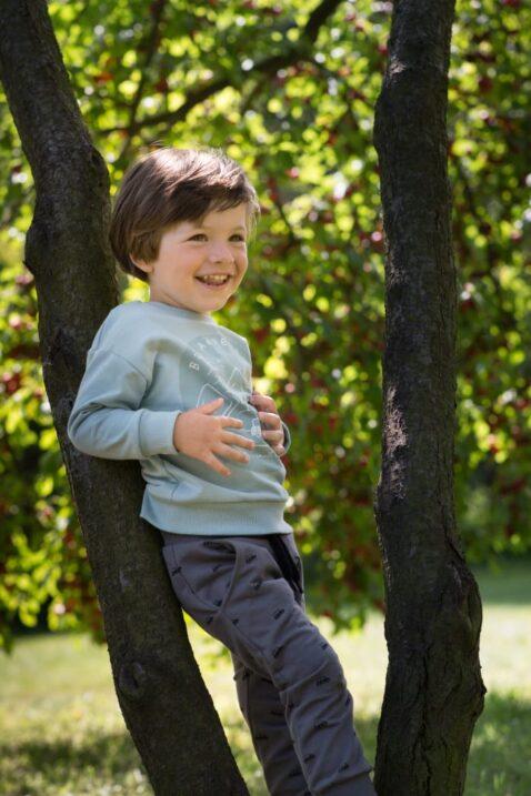 Stehender Junge trägt graue baby Pumphose mit Taschen & Autos Muster - Blau Mint grünes Sweatshirt Kinder Oberteil langarm ADVENTURE CAR von Pinokio - Babyphoto Kinderphoto