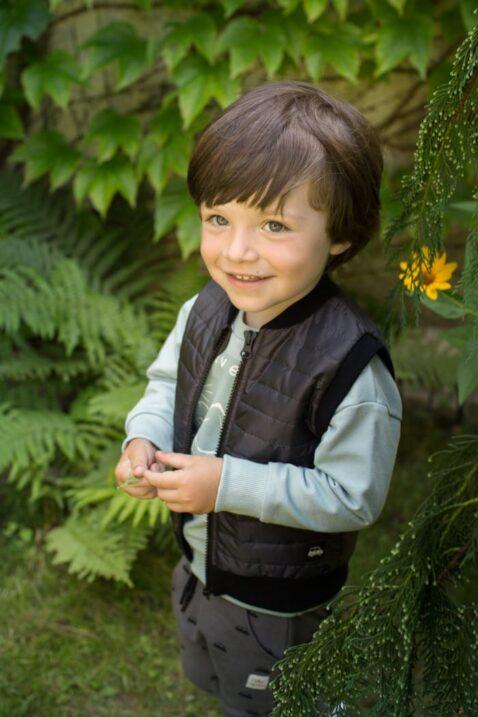 Junge trägt süße schwarze Steppweste mit Auto & Reißverschluss - Grau braune Pumphose Haremshose mit Cars - Mint grünes langarm Sweatshirt mit Print Adventure, Berge von Pinokio - Babyphoto Kinderphoto