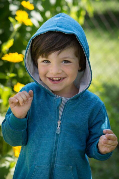 Lachender Junge trägt blauen Kinder Babyoverall mit Kapuze, ohne Fuß, Kängurutasche, Reißverschluss & Auto Patch aus Baumwolle von Pinokio - Babyphoto Kinderphoto