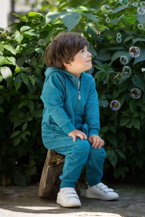 Sitzender Junge trägt türkis blauen Baby Baumwoll Strampler ohne Fuß mit Kapuze, Kängurutasche, Reißverschluss & Retro Auto Car Patch von Pinokio - Babyphoto Kinderphoto