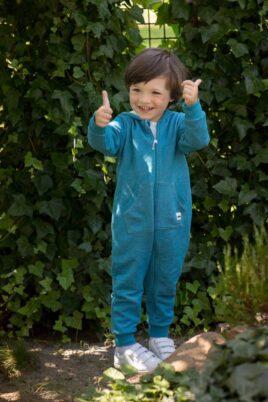 Stehender Junge trägt blauen Kinder Baby Strampler ohne Fuß, mit Kapuze, Reißverschluss, Kängurutasche & Auto Patch aus hochwertiger Baumwolle von Pinokio - Babyphoto Kinderphoto
