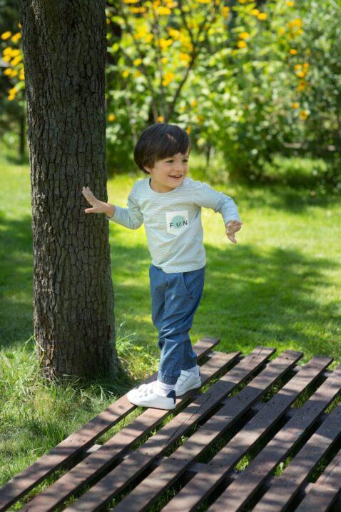 Spielender Junge mit blauer Denim Babyhose mit Tasche Jeans Optik & Auto Patch - Kinder Langarmshirt blau-weiß gestreift mit Brusttasche von Pinokio - Babyphoto Kinderphoto