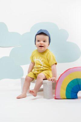 Strahlender Junge trägt Baby Jeansmütze mit SUN & FUN Patch - Gelber Sommer Romper Kurzarm-Spieler mit lachender Sonne von Pinokio - Babyphoto Kinderphoto