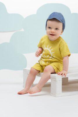 Lächelnder Junge trägt Kindermütze mit Schirm in Jeansblau - Hochwertiger Baby Romper Spieler kurzer Overall mit Sonne Gelb von Pinokio - Babyphoto Kinderphoto