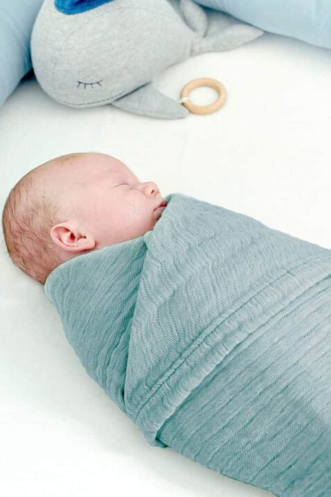 Baby eingewickelt in dunkelgrüner Babydecke Musselin aus OEKO Tex Baumwolle - Grünes funktionelles 4-in-1 Spucktuch, Stilltuch, Spieldecke & hochwertiges saugfähiges Pucktuch von Nordic Coast Company - Babyphoto