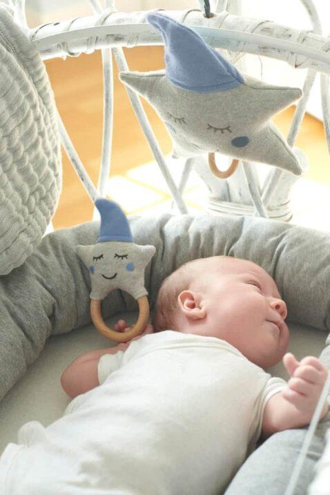 Schlafendes Baby mit blau-grau Holz Beißring Babyrassel & einer Spieluhr mit Melodie Guten Abend Gute Nacht in Sterne-Optik aus zertifizierter OEKO TEX Baumwolle von Nordic Coast Company - Babyphoto