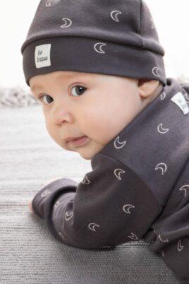 Baby Junge trägt graubraune Zipfelmütze Baumwollmütze mit Halbmonden & Patch BE BRAVE - Kinder Schlafoverall mit Druckknöpfen & Füßen OEKO TEX von Pinokio - Babyphoto Nahaufnahme