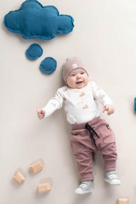 Baby Junge trägt beige Pumphose mit Taschen & Berge Patch - Weißen Wickelbody langarm mit Bergpanorama gemustert - Beige Babymütze mit Umschlag BE BRAVE Baumwolle von Pinokio - Kinderphoto liegender Junge