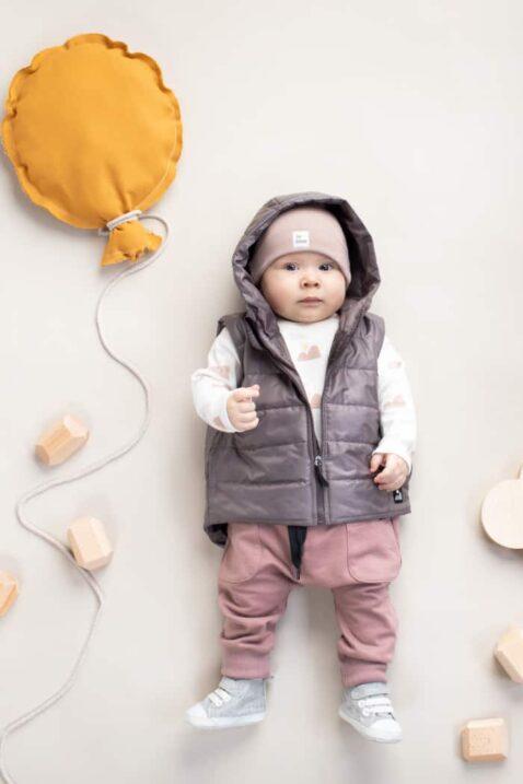 Baby Junge trägt graue Steppweste mit Kapuze - Pumphose mit Taschen & Patch Berge - Beige Kindermütze mit Umschlag aus Baumwolle OEKO TEX von Pinokio - Liegender Junge Babyphoto