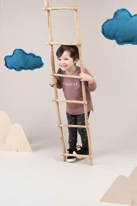 Kind Junge trägt graphit graue Leggings Babyhose mit Monden Muster - Dunkelbeiges Langarm Baby Baumwoll Oberteil Sweatshirt mit Taschen vorne von Pinokio - Kinderphoto lachender Junge