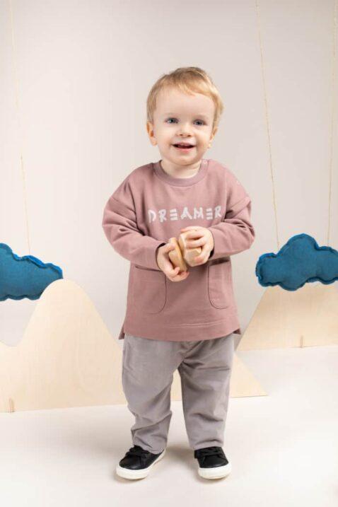 Junge trägt Baumwolloberteil Pullover langarm beige mit zwei Vordertaschen & DREAMER Schriftzug - Graue Kinder Cord Babyhose & Gummizug von Pinokio - Babyphoto lachender Junge