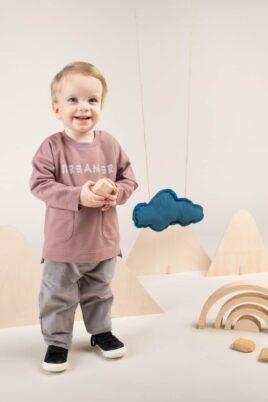 Kind Junge trägt Baby Cordhose in Grau - Pullover Beige Sweatshirt langarm mit Taschen vorne & längere Rückseite Oberteil aus 100% hochwertiger Baumwolle OEKO TEX von Pinokio - Babyphoto stehender Junge