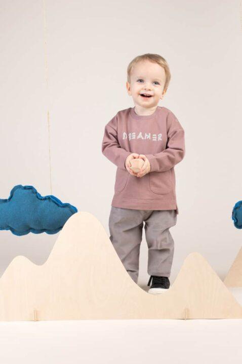 Kind Junge trägt Cordhose in Grau - Sweatshirt Pullover DREAMER Print mit Taschen & länger geschnittener Rückseite Langarmoberteil aus 100% Baumwolle Rundhalsausschnitt von Pinokio - Babyphoto lächelnder Junge
