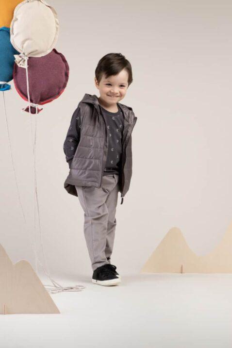 Junge trägt graue Steppweste mit Kapuze - Langarmoberteil Sweatshirt Rundhals mit Halbmonden gemustert - Kinderhose Cordhose grau von Pinokio - Kinderphoto stehender Junge