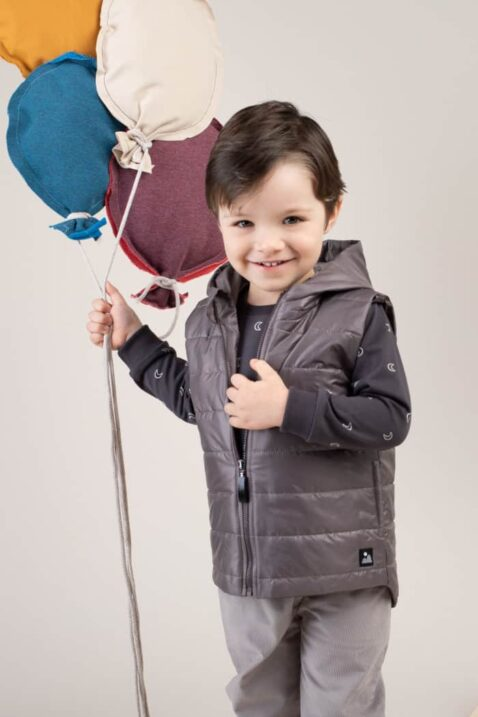Junge trägt Kinder Steppweste ärmellos mit Kapuze Grau - Dunkelgrauer Kinderpullover langarm Sweatshirt mit Monden Himmel hochwertig & günstig von Pinokio - Kinderphoto Nahaufnahme