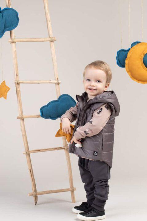 Junge trägt graue Kinder Baby Pumphose Jogger mit Taschen - Graue Kapuzen-Steppweste - Langarmshirt mit Berg-Motiven in Beige aus Baumwolle von Pinokio - Babyphoto Kinderphoto