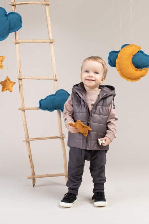 Junge trägt Kinder Steppweste mit Kapuze in Grau - Baby Haremshose Sweathose lang mit Taschen & Berge Patch - Oberteil aus Baumwolle gemustert von Pinokio - Kinderphoto lachender Junge