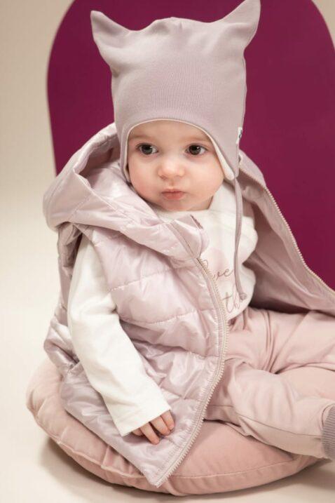 Baby Mädchen trägt rosa Steppweste mit Kapuze ohne Ärmel & Taschen - Langarm Wickelbody weiß mit Blume & Print LOVE IN THE AIR - Mütze mit Ohren & Blume-Patch grau von Pinokio - Babyphoto sitzendes Mädchen
