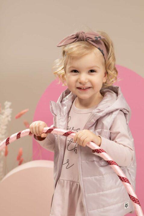 Baby Mädchen trägt rosa Steppweste mit Kapuze & Taschen in Rosa - Tunika Langarmshirt in Kleidchenoptik mit Print LOVE IN THE AIR - Stirnband mit Schleife & Blumen gemustert von Pinokio - Baby Kinderphoto