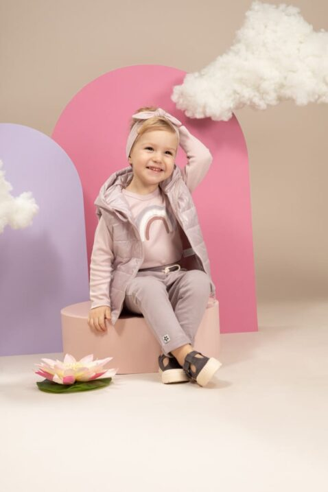 Mädchen trägt rosa Stirnband mit Schleife unifarben - Kinder Kapuzen-Steppweste mit Taschen rosa - Langarmshirt mit Regenbogen - Baby Sweathose mit großen Taschen in Grau von Pinokio - Kinderphoto lachendes sitzendes Mädchen