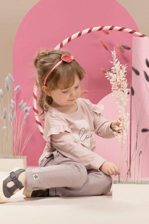 Mädchen trägt graue Baumwoll Sweathose Babyhose mit Taschen, Beinumschlag & Blumen Patch - Rosa Kinder Oberteil langarm mit Rüschen & LOVE Print von Pinokio - Babyphoto spielendes Mädchen mit Hula-Hoop-Reifen