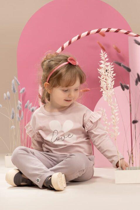 Mädchen trägt rosa Langarmshirt mit Rüschen & LOVE Blumen Print - Graue Sweathose Babyhose mit Taschen, Blumen Patch & Beinumschlag aus Baumwolle von Pinokio - Babyphoto sitzendes Mädchen