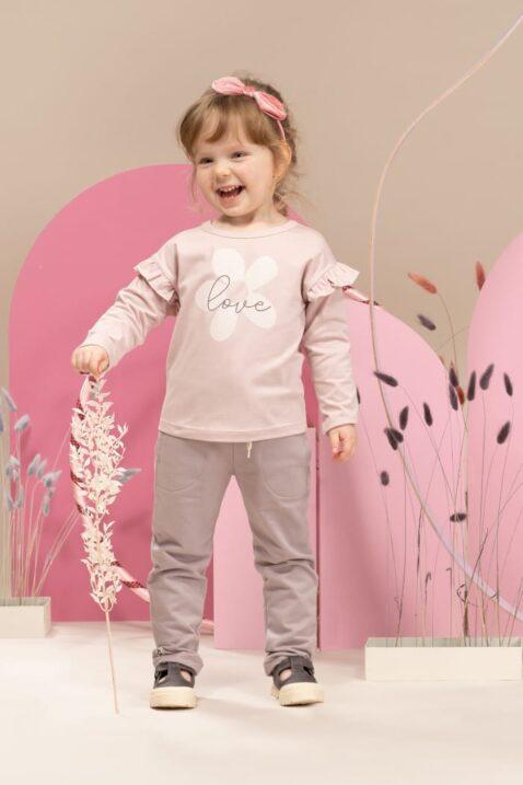 Mädchen trägt steingraue Babyhose Schlupfhose mit großen Taschen, Beinumschlag & Kordel Komfortbund - Hellrosa Langarmshirt mit Rüschen & LOVE Blumen Print Rundhalsausschnitt von Pinokio - Kinderphoto stehendes lachendes Mädchen