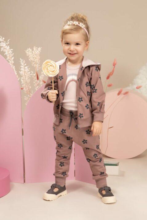 Mädchen trägt rosa Pumphose Babyhose mit Taschen & Blumenmuster - Regenbogen Langarmbody hellrosa - Dunkelrosa Kapuzen-Sweatjacke mit Blumen, Reißverschluss & Kinnschutz aus Baumwolle von Pinokio - Kinderphoto stehendes Mädchen