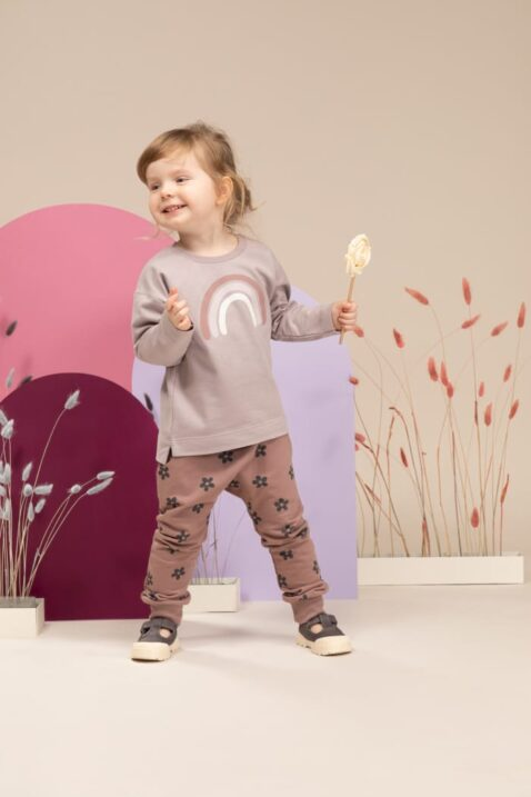 Mädchen trägt rosa Rundhals Baby Kinder Langarmshirt mit Regenbogen - Dunkelrosa Kinder Blumen Haremshose Schlupfhose mit Taschen, Kordel & breiten Bündchen von Pinokio - Kinderphoto lachendes Mädchen