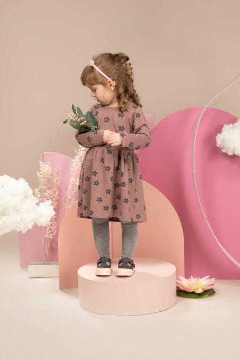 Mädchen trägt weißen Kinder Haarreif mit Perlen - Basic Leggings Grau - Braunrotes Babykleid langarm knielanges Blumenkleid gemustert von Pinokio - Kinderfoto Mädchen mit Blumen