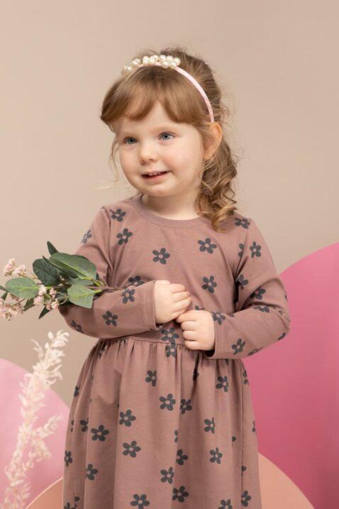 Mädchen trägt rosa Babykleid knielang mit langen Ärmeln & Blumenmuster - Kinder Leggings Basic grau - Haarreifen mit Perlen in weiß von Pinokio - Kinderfoto Nahaufnahme
